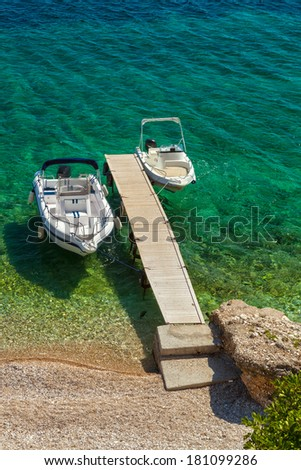 Empty boats standing at wooden pier under bright sunlight with shadow on pebbles at sea floor seen through transparent water of Ionian sea, Corfu, Greece - stock photo