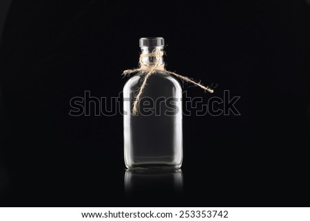 empty bottle tied with rope isolated in black   - stock photo