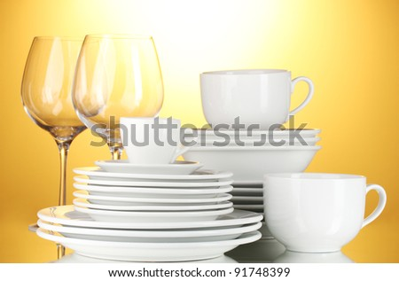 empty bowls, plates, cups and glasses on yellow background - stock photo