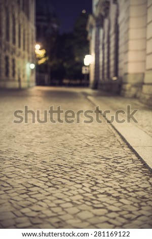 empty brick road at night with blurred background, vintage filtered style, historic midtown of Berlin, Germany, Europe - stock photo