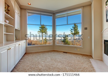 Empty bright room with beige carpet floor, angled glass wall and wood storage combination