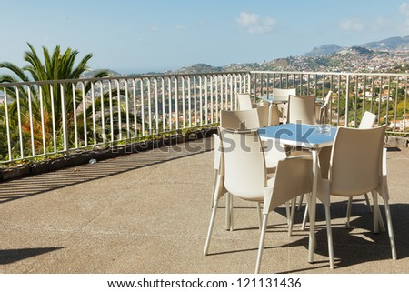 Empty cafe tables high over Funchal city and Atlantic ocean, Madeira, Portugal
