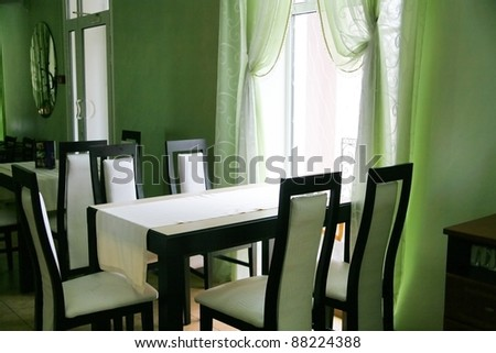 Empty cafe with a table and chairs illuminated with light from a window