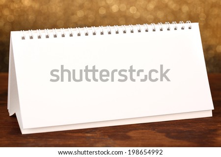 Empty calendar on wooden table on shiny golden background
