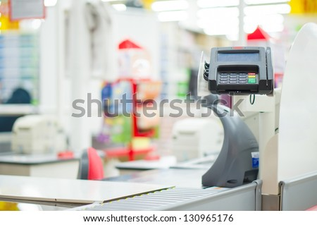 Empty cash desk with card payment terminal in supermarket - stock photo