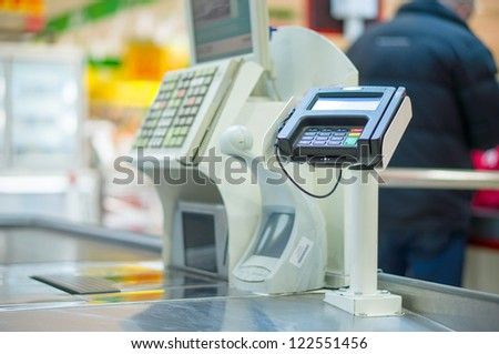 Empty cash desk with terminal in supermarket - stock photo