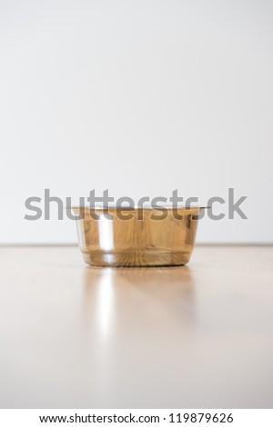 Empty cats steel bowl on wooden floor. Lot of copyspace. Lost pet concept vertical - stock photo