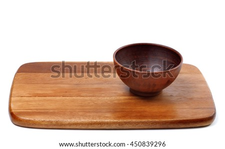 Empty ceramic bowl on wooden kitchen board. Isolated on white background. - stock photo