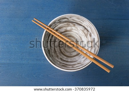 Empty ceramic bowl with bamboo chopsticks over blue wooden surface. Top view - stock photo