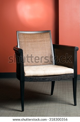 Empty chair in dramatic lighting in front of a an orange wall.  - stock photo