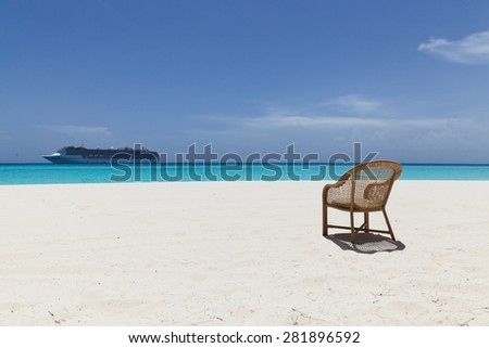 empty chair on beach with cruise ship in the background and clear water