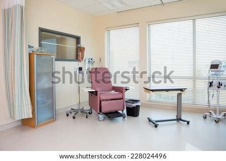 Empty chair with IV drip stand and table in chemo room - stock photo