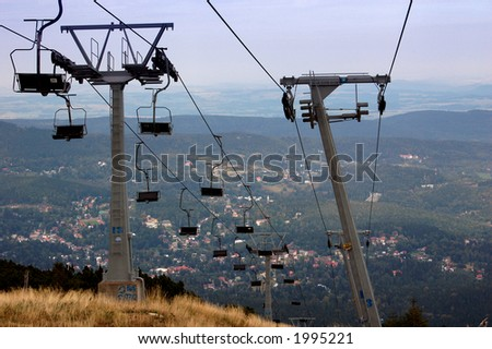 Empty chairlift and view from the mountain on the city below.