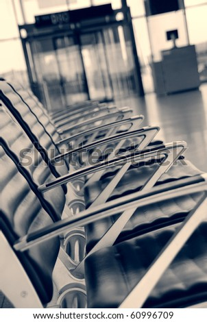 Empty chairs at the airport, entrance in the background/Airport - stock photo