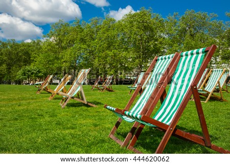 Empty chairs on a lawn of a beautiful park in summer - stock photo