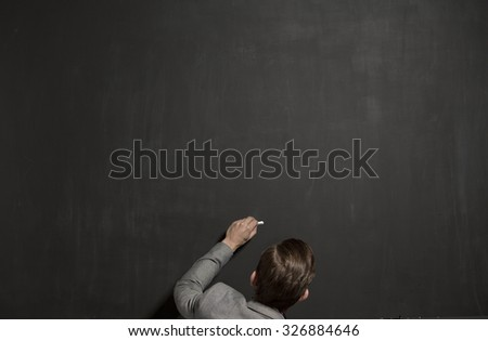 empty chalk black board with chalk in the hand - stock photo
