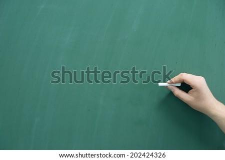 empty chalkboard with hand and chalk / Chalkboard - stock photo