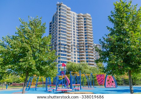 Empty children playground with ladders, climbing stairs and slides. Kids and toddlers place to have fun and play in summer. Playground near high block building. Bright sun, clear sky, hard shadows. - stock photo