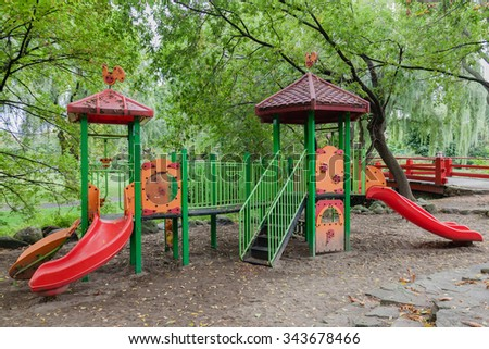 Empty children playground with ladders, climbing stairs and slides. Kids and toddlers place to have fun and play in summer. Playground in the shadow of the trees. - stock photo