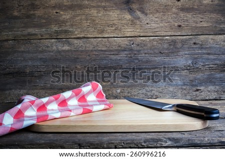 Empty chopping board with a sharp paring knife and napkin on a distressed grunge wooden table - stock photo