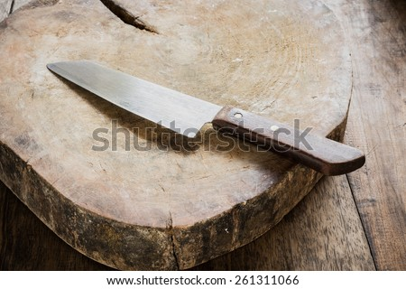 Empty chopping board with a sharp paring knife on a distressed grunge wooden table in a rustic kitchen, overhead view with a vignette