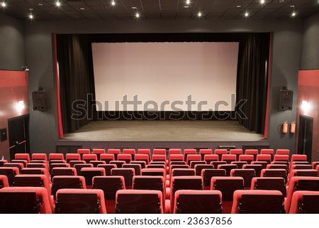 Empty cinema auditorium with line of chairs and stage with silver screen. Ready for adding your own picture. - stock photo