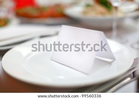 Empty classic white plate in a restaurant with a blank card and copyspace for example guest names. - stock photo