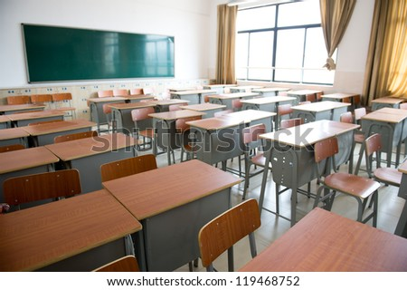 Empty classroom with chairs, desks and chalkboard. - stock photo
