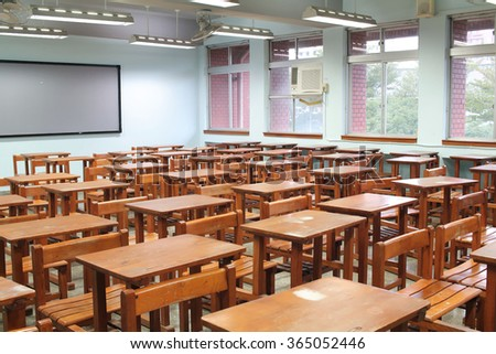 Empty classroom with desks and chairs - stock photo