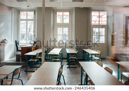 Empty classroom with large windows and old furniture - stock photo