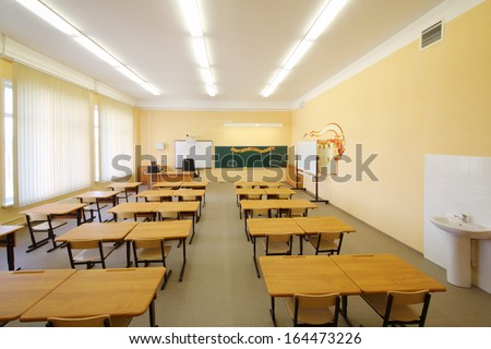 Empty classroom with wooden desks, chalk board and yellow walls in school. - stock photo