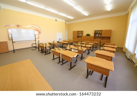 Empty classroom with wooden desks, white chalk board and bookcases in school.
