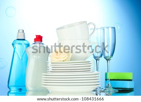 empty clean plates, glasses and cups with dishwashing liquid and sponges on blue background - stock photo