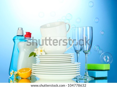 empty clean plates, glasses and cups with dishwashing liquid, sponges and lemon on blue background - stock photo
