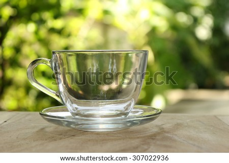 Empty clear glass of tea on bokeh green leaf background. - stock photo