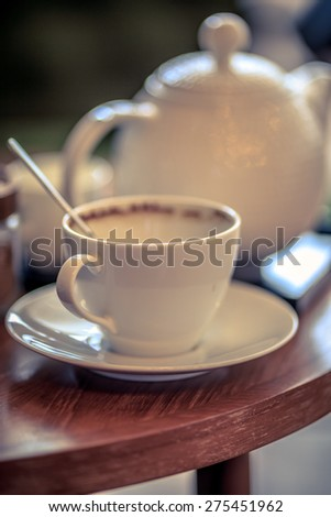 Empty coffee cup and jug behind blurry on the wood desk White utensil on cafe coffee in the morning ,spoon in cup - stock photo