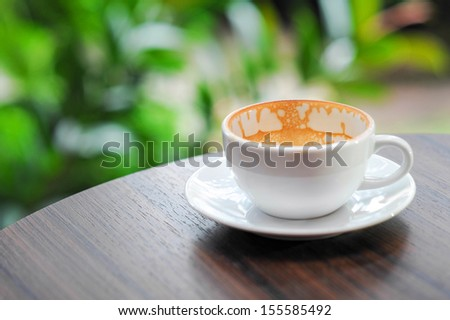 Empty coffee cup on the wood garden table - stock photo