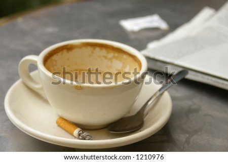 empty coffee cup with cigarette butt - stock photo