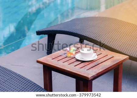 Empty coffee cup with sweet candy on wooden table neear swimming pool in summer. - stock photo