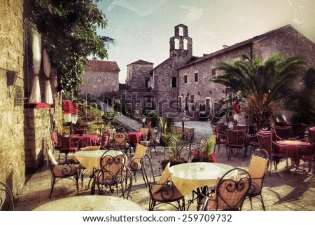 Empty coffee terrace with tables and chairs in old town of Budva on sunny day at sunset, Montenegro. Filtered image, vintage effect applied. Grunge - stock photo