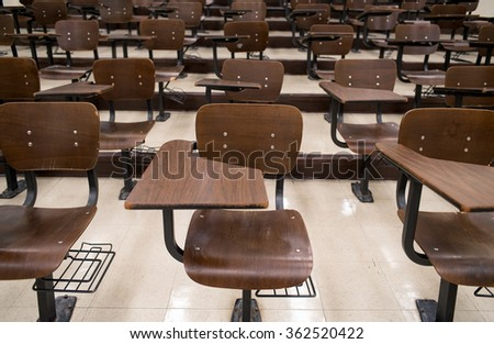 Empty college classroom with well-used chairs and desks.