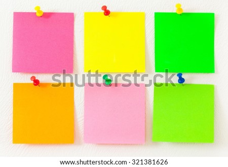 Empty colorful post its on the wall with push pins. - stock photo