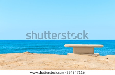 Empty concrete bench overlooking the blue water. Calm ocean. Clear blue sky and horizon. Room for text, copyspace.  - stock photo