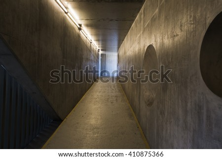 Empty concrete tunnel with neon lights and geometric shapes on a wall - stock photo
