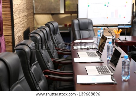 Empty conference room with laptops on table