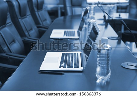 Empty conference room with laptops on table in shades of grey - stock photo