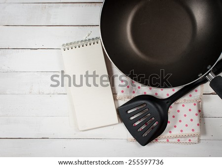 Empty cooking frying pan with turner on wooden background - stock photo