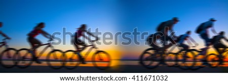 Empty Copy Space Sporty company friends on bicycles outdoors against sunset Silhouette eight 8 cyclist going along shoreline coast Reflection sun on water Sport in Nature background Group of people - stock photo