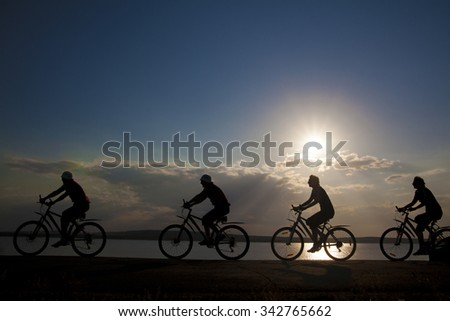 Empty Copy Space Sporty company friends on bicycles outdoors against sunset Silhouette four 4 cyclist going along shoreline coast Reflection sun on water Sport in Nature background Group of people - stock photo
