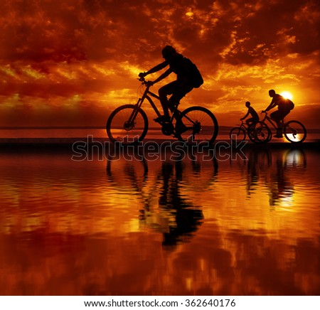 Empty Copy Space Sporty company friends on bicycles outdoors against sunset Silhouette three 3 cyclist going along shoreline coast Reflection sun on water Sport in Nature background Group of people - stock photo